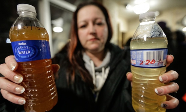 LeeAnne Walters shows water samples from her home from 21 January and 15 January after city and state officials spoke during a forum discussing growing health concerns being raised by residents about the water. Photograph: Ryan Garza/AP